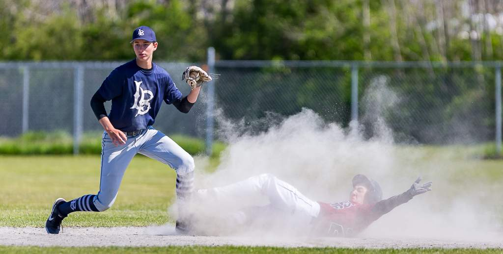 April 28, 2019, Victoria, BC - Langley shortstop Kai Cumiskey shows the umpire the ball, while in a cloud of dust, Eagles baserunner Ryan Whelan tries to get the safe call on this play at second. Whelan was out on the play (Photo: Christian J. Stewart)