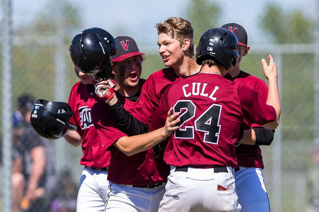 April 28, 2019, Victoria, BC - The Victoria Eagles' Brandon LeBlanc is swarmed by his teammates after his two-run homer gave the Eagles a 2-1 lead (Photo: Christian J. Stewart)