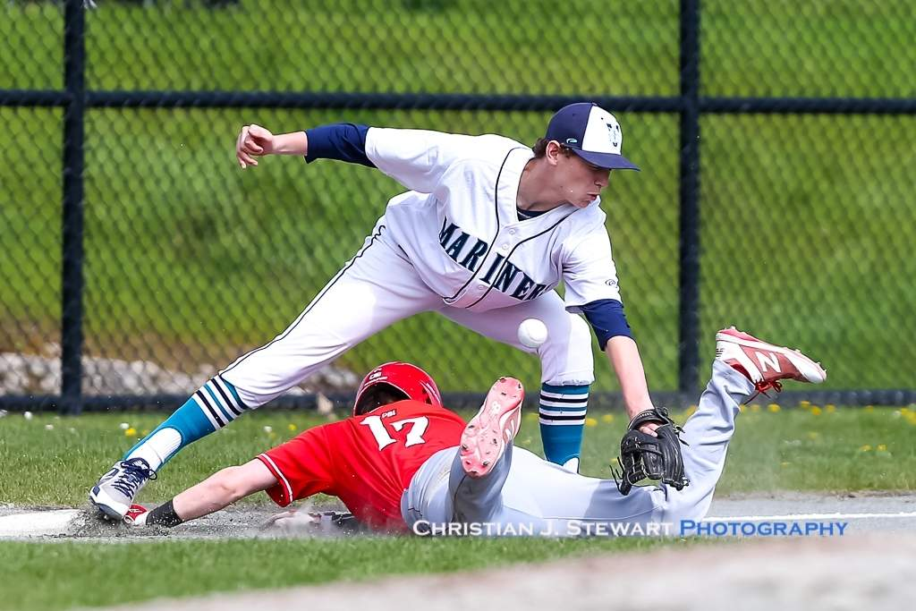 April 21, 2019, Victoria, BC - The Reds Will Ireland (17) slides safely into third in game one Sunday as the ball gets away from Mariners third baseman Taine Clague (Photo: Christian . Stewart)