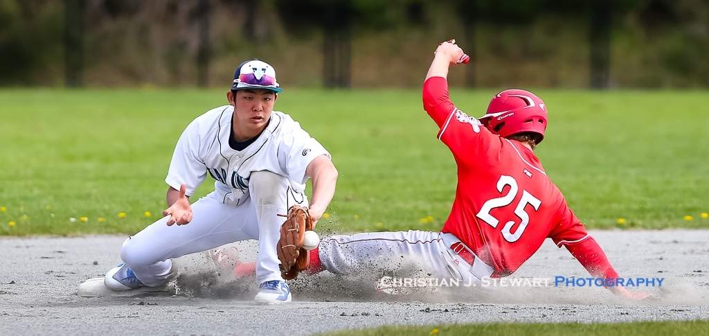 April 21, 2019, Victoria, BC - The Reds Jack Yaremko (25) slides safely into second as the ball gets away from the Mariners second baseman Rei Kimura on this play in game two Sunday (Photo: Christian J. Stewart)