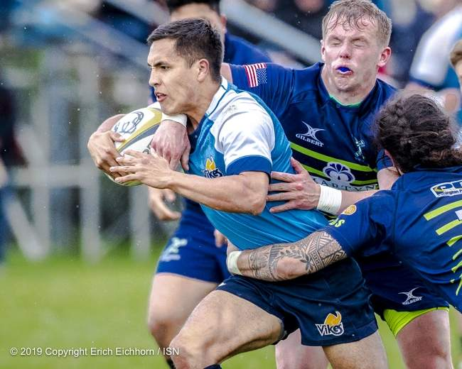 April 6, 2019   Victoria, BC (ISN) - Ever-dangerous in the open field Uvic's scrum half Crosby Stewart breaks through two Seattle tacklers - Erich Eichhorn image (www.allsportmedia.ca)