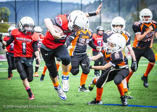 May 4th, 2019 Victoria, BC (SN) - Warriors Austin Perry dances around a pair of Lion defenders on his way to one of his two TD's in the game - Erich Eichhorn image ( www.allsportmedia.ca)