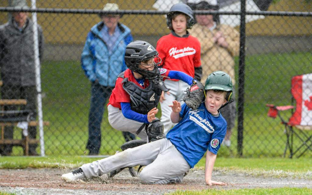 Lakehill 2 catcher, Hudson Peters makes the tag on Hampton's player during the bronze medal game. Photo by Gord Rufh ISN Sports