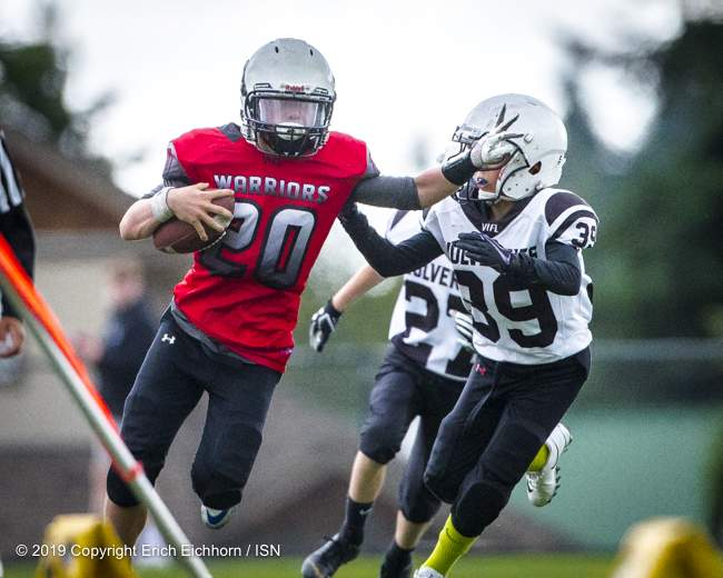 June 23rd, 2019 Ladysmith, BC (ISN) - Warrior's Austin Perry gets the better of a hopeful Wolverine tackler - Erich Eichhorn image (www.allsportmedia.ca )