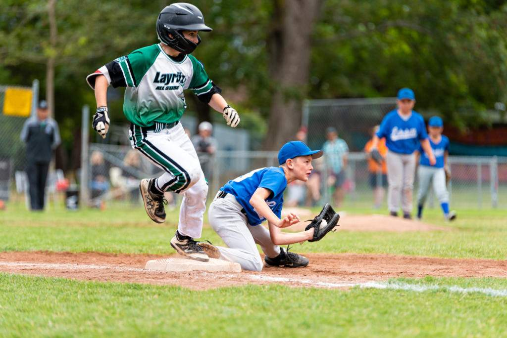 Devon Simonovic of Layritz beats the ball of Lakehill's first baseman Ben Smith. Photo by Gord Rufh ISN Sports