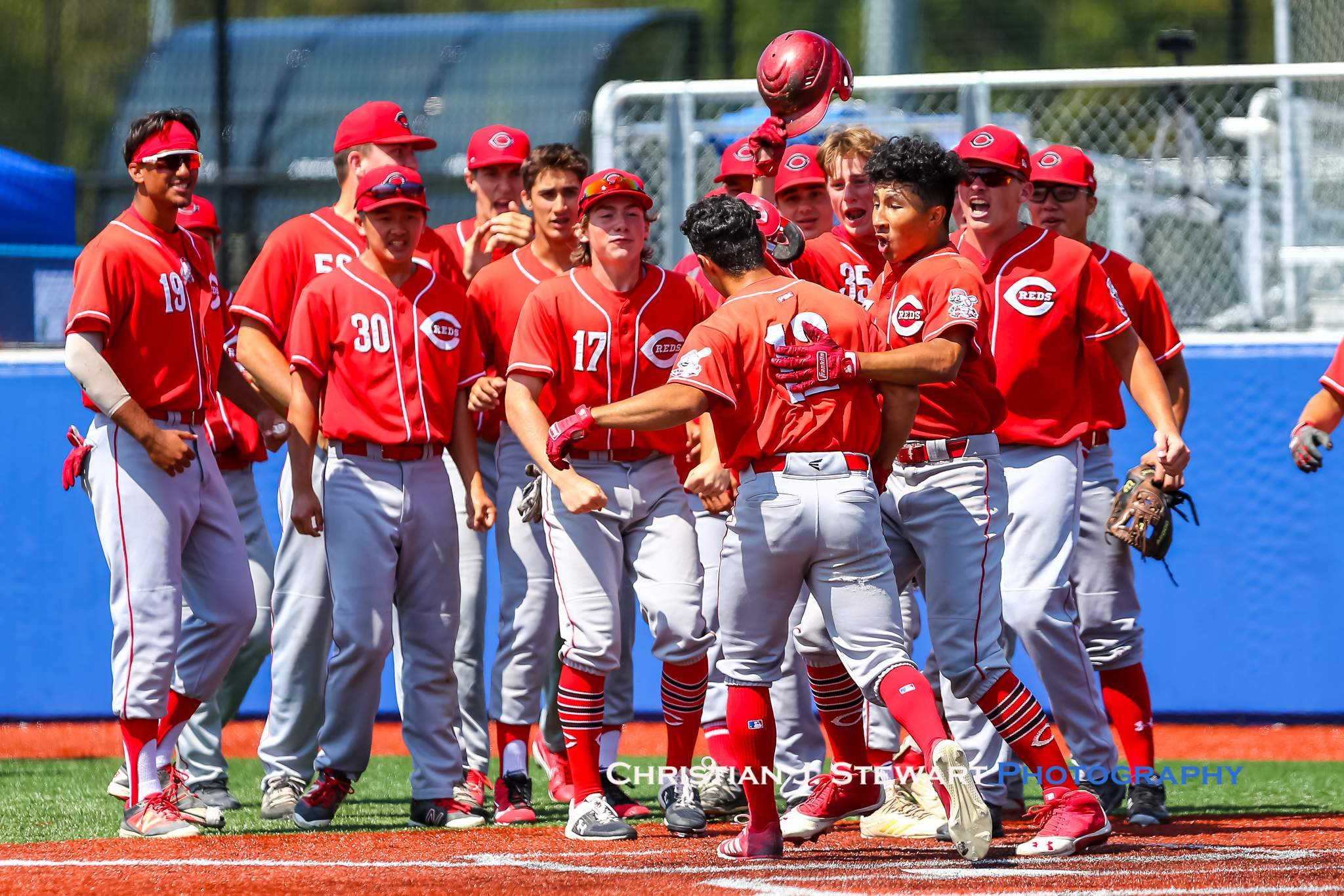 Coquitlam's Luciano Letteri (12) is mobbed by his teammates after his two-run home run tied the game in the top of the fifth inning (Photo: Christian J. Stewart)