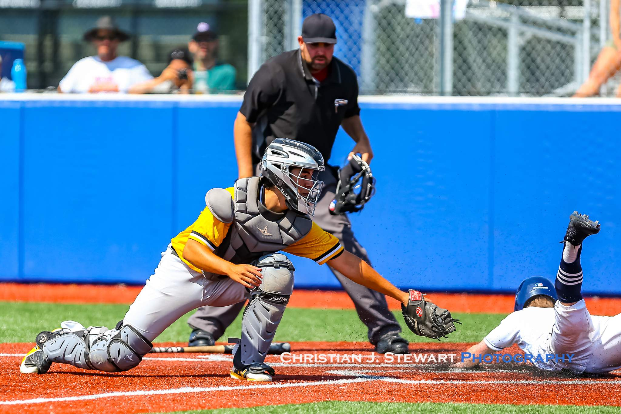 The Thunder's Trew Petersen sneaks past the tag of Mid-Island catcher Matthew Simpson to score the first run of the game Sunday (Photo: Christian J. Stewart)