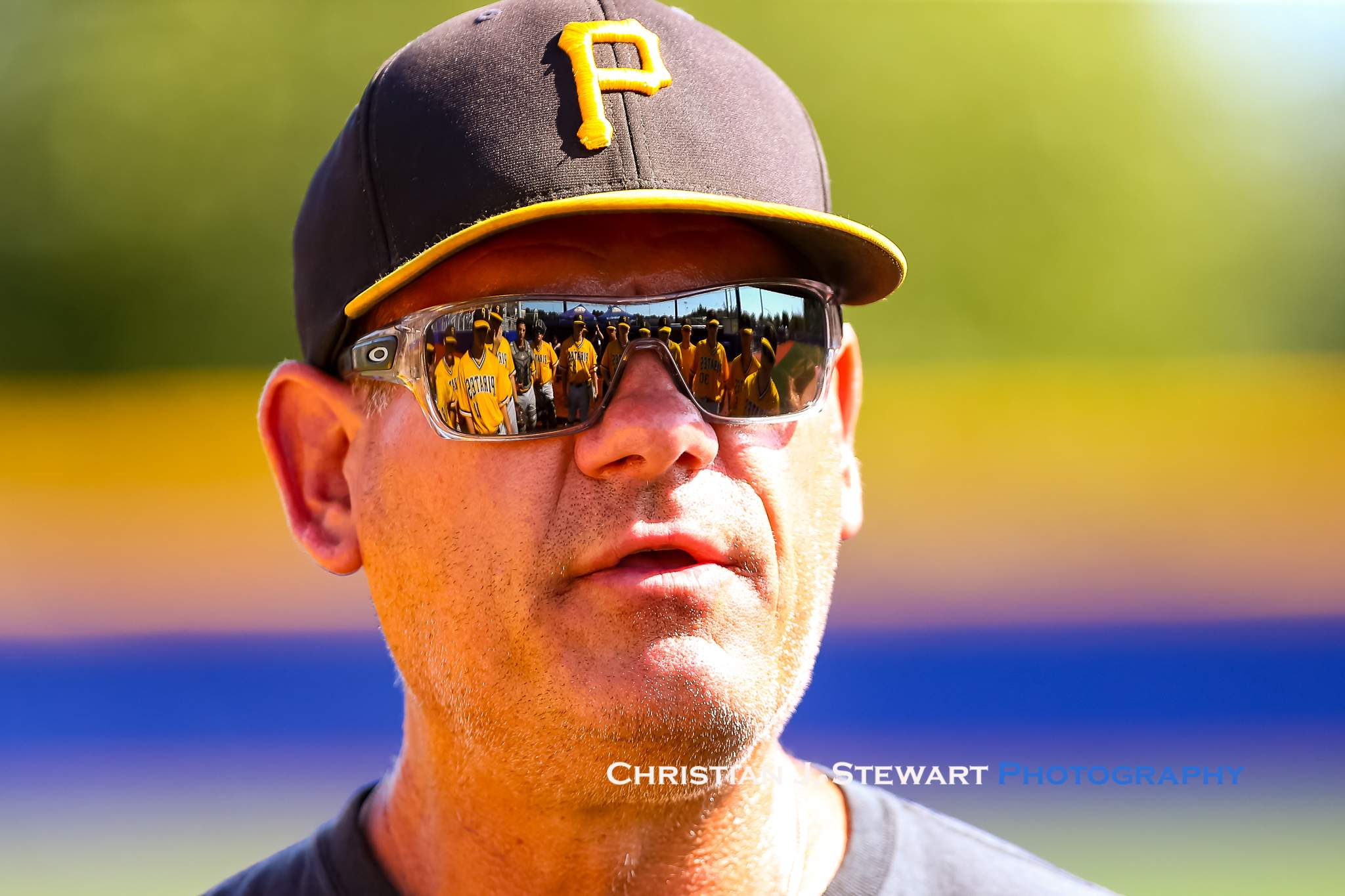 With his team reflected in his sunglasses, Pirates Head Coach Doug Rogers delivers some motivation late in Sunday's game (Photo: Christian J. Stewart)