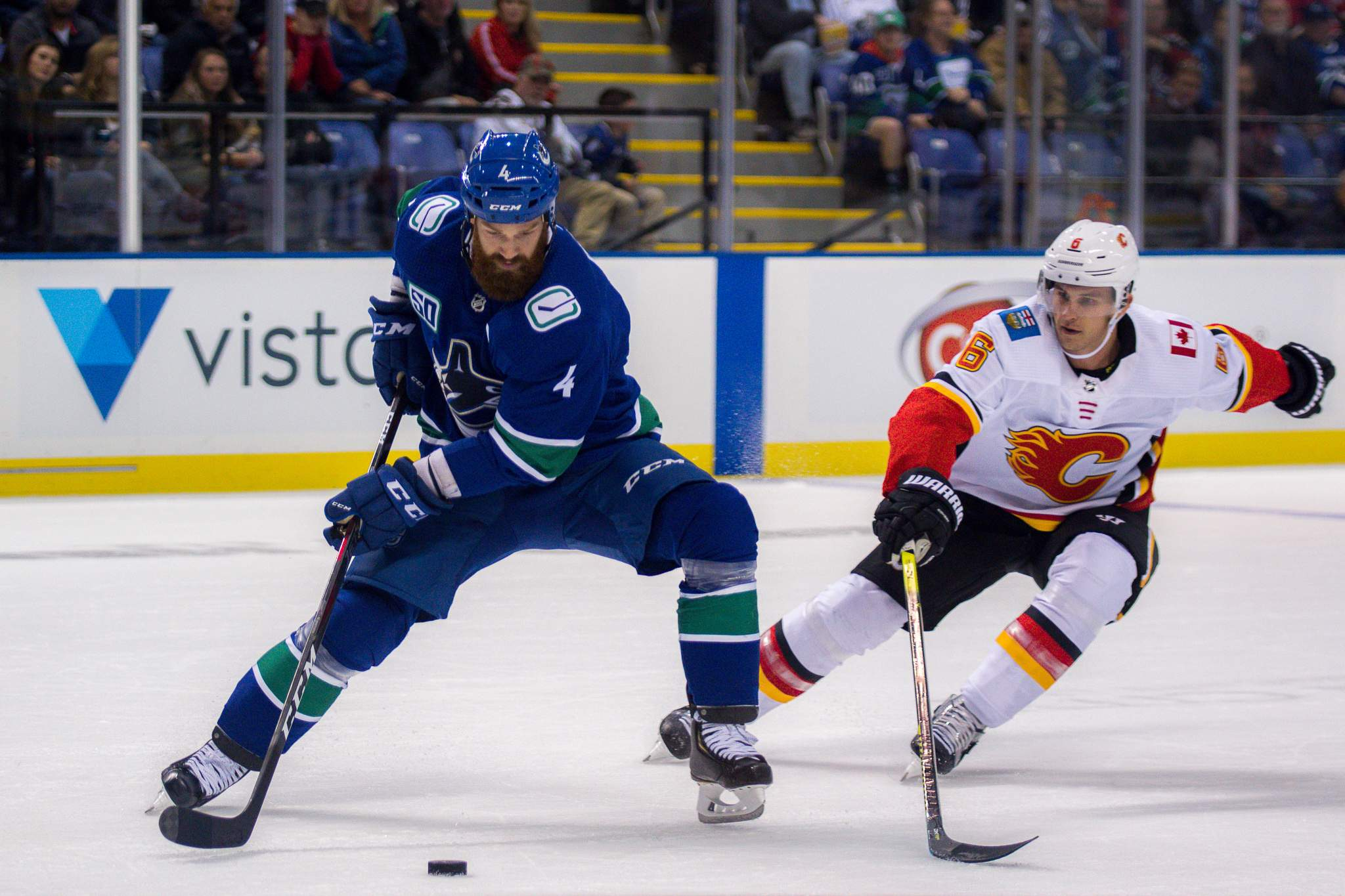 Canucks' Jordie Benn defends the puck from Flames' Brandon Davidson. Photo by Nathanael Laranjeiras