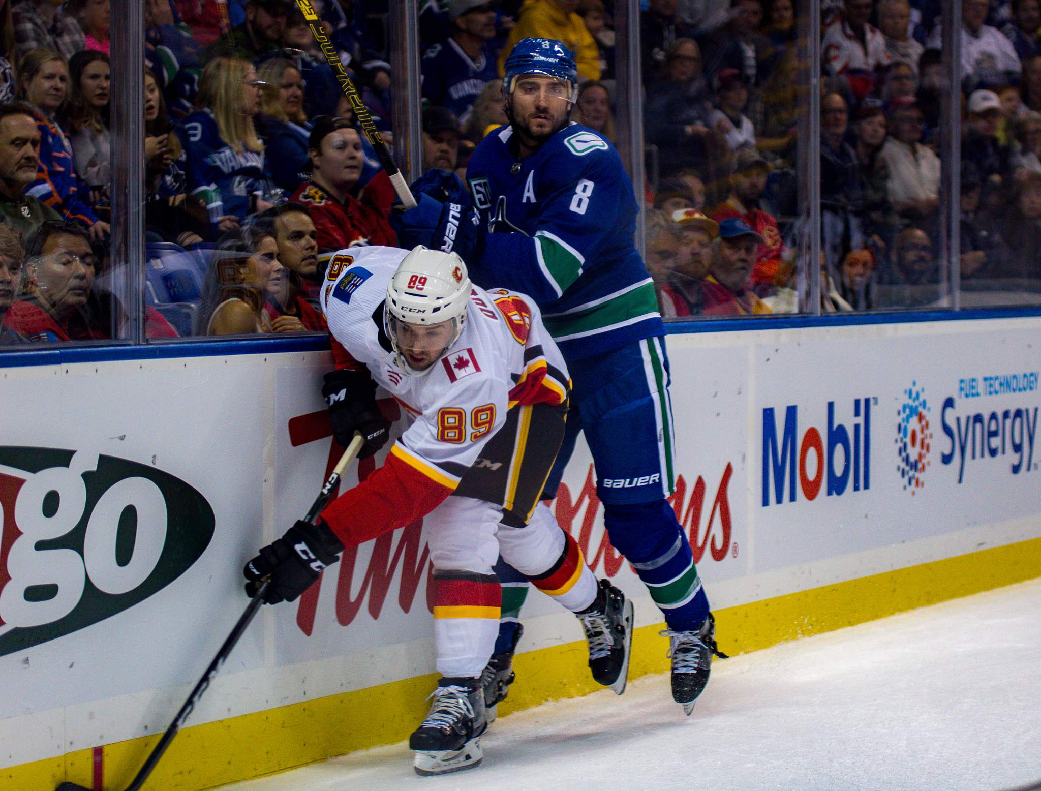 Canucks' Chris Tanev battles Flames' Alan Quine for the puck. Photo by Nathanael Laranjeiras (ISN)
