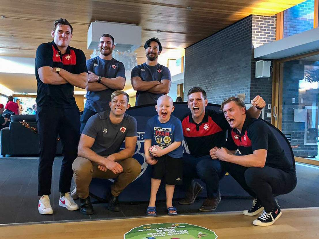 (L-R) Phil Berna, Isaac Kaay, Nathan Hirayama, Harry Jones, Adam Zaruba and Josh Thiel of Canada Men's Sevens Team share a laugh with a new rugby fan from the Ronald McDonald House BC and Yukon. Credit: Rugby Canada
